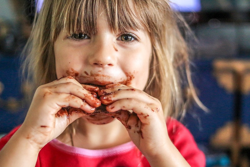 Little girl eating chocolate has got chocolate all around her mouth and on her hands.