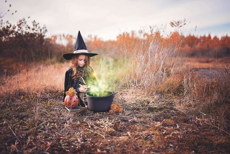 Little girl dressed as a witch sat on the ground in a field making a green potion in a cauldron.