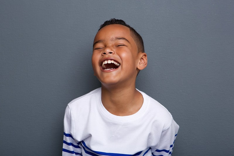 Young boy standing in front of a grey background laughing at history jokes.