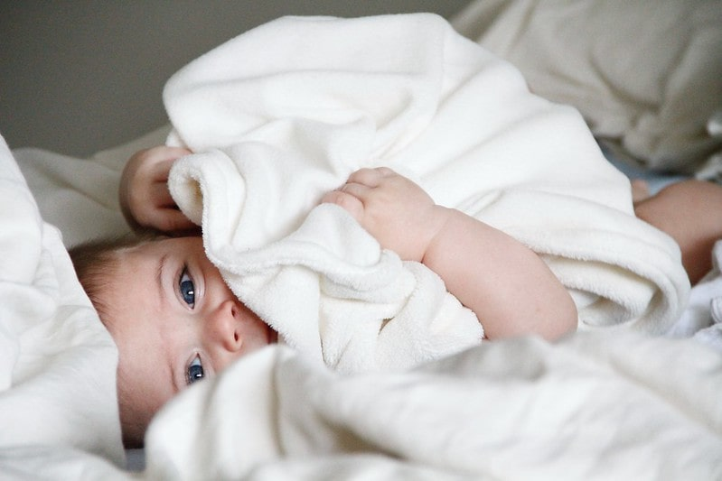 Baby lying on the bed under a white towel.