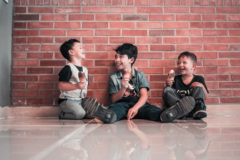 Three boys sitting on the floor by a wall eating ice cream and laughing together.