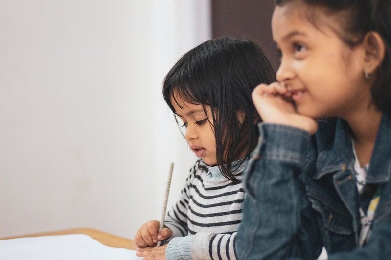 Two young girls sat at a desk learning and writing notes in the classroom.