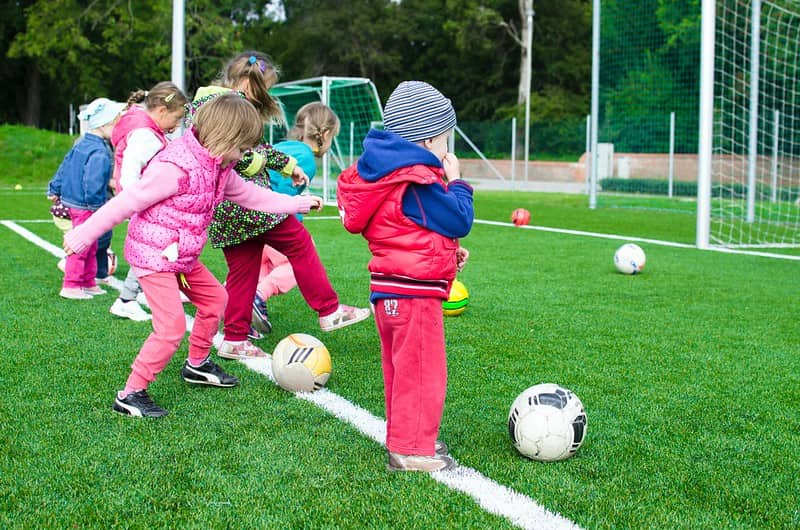 Small children outside kicking footballs during a PE lesson.
