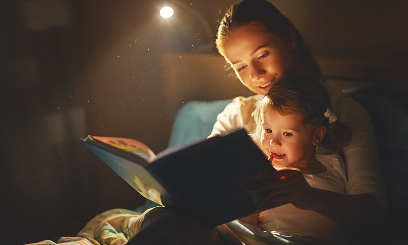 Mum sat in bed with her daughter reading to her from a book.