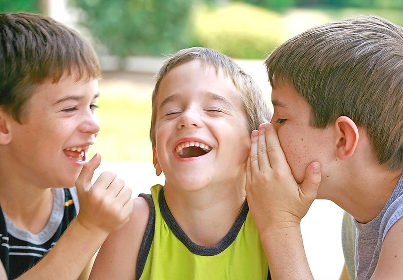 Three boys sharing Spiderman jokes with each other and laughing.