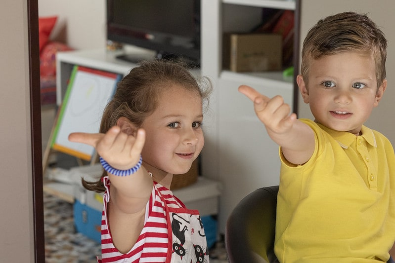 A little girl and boy doing Spiderman hands, pretending to shoot webs from their fingers.