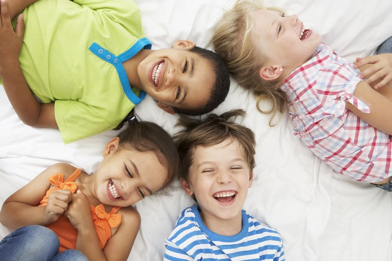 Four kids lying on a bed laughing at Spiderman jokes.