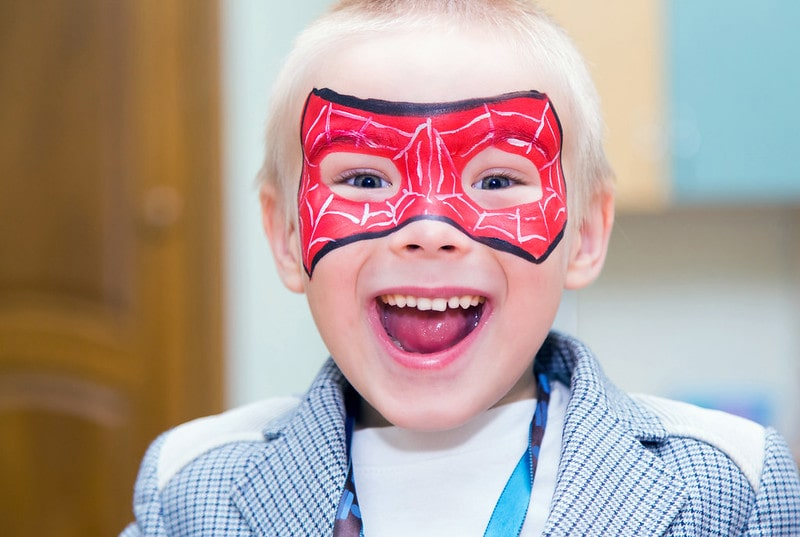 Boy with Spiderman mask face paint smiling happily.