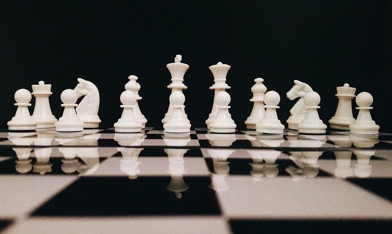 Full set of white chess pieces on a chess board.
