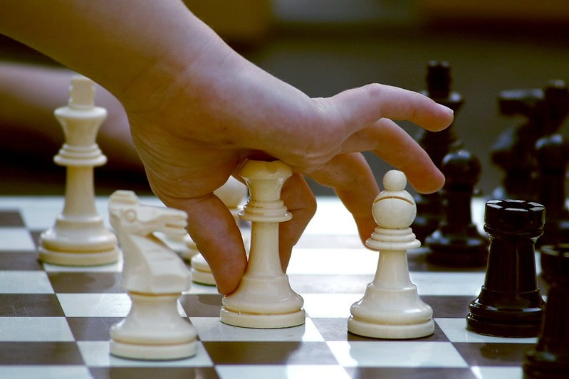 Close up of a child's hand as they pick up a chess piece to make a move.
