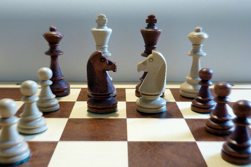 Wooden chess set with the pieces all lined up.