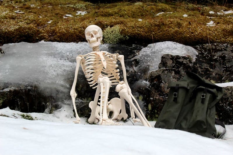 A funny skeleton sat in the snow leaning against some rocks.