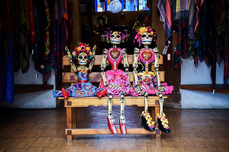 Three skeletons dressed for the Mexican festival 'Día de los Muertos' (Day of the Dead) sitting on a bench.