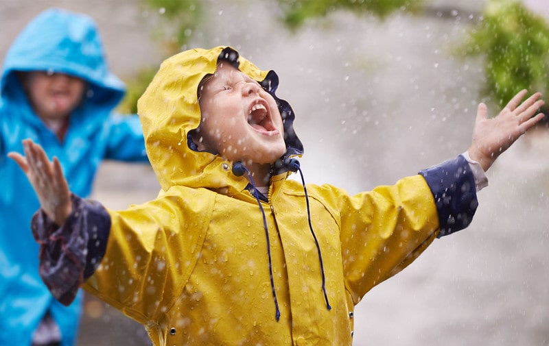 Kids wearing raincoats messing around and getting wet in the rain.