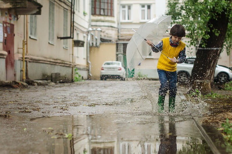 Young boy holding an umbrella splashes around in a puddle on the street in his wellies.