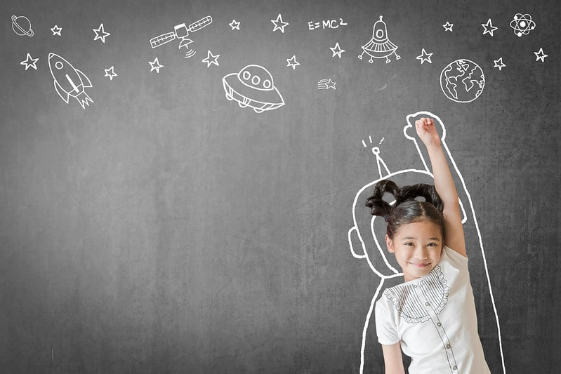 Little girl standing in front of an outline of an astronaut suit drawn on a blackboard with stars and spacecrafts drawn above.