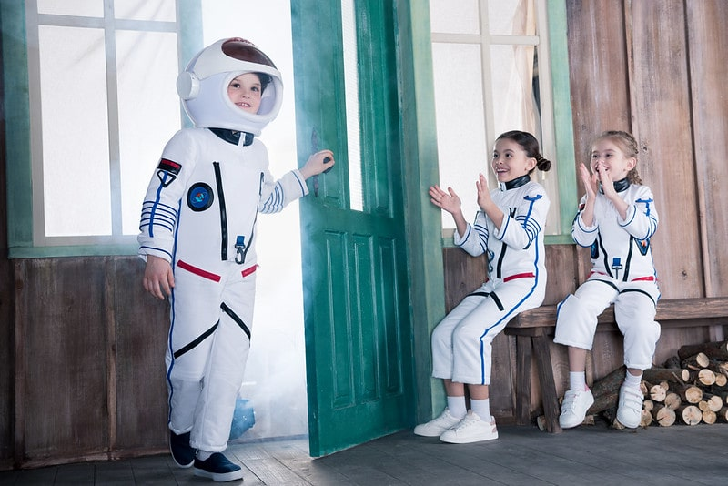 Three kids in astronaut costumes happy and enjoying themselves.