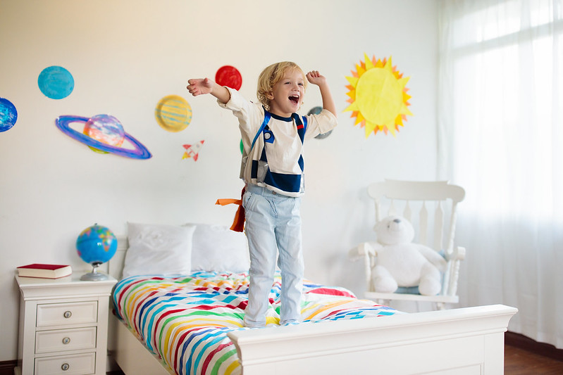 Boy in astronaut clothing standing on the bed in his space-themed room.