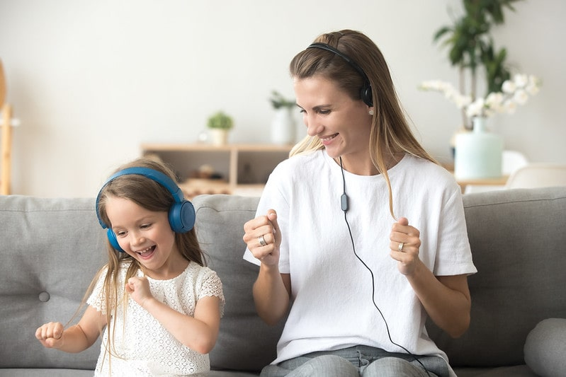 Mum and daughter sat on the sofa each listening to headphones to learn phonics.