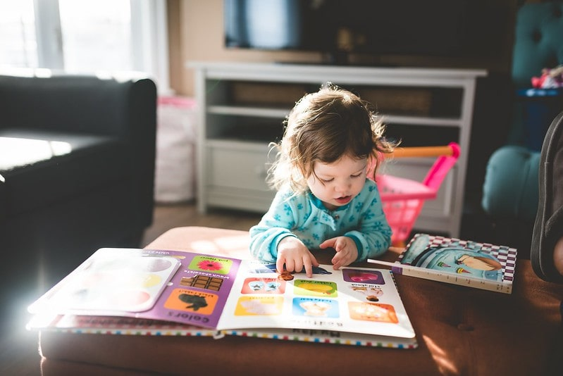 Little girl learning to read, looking at a book on the table.