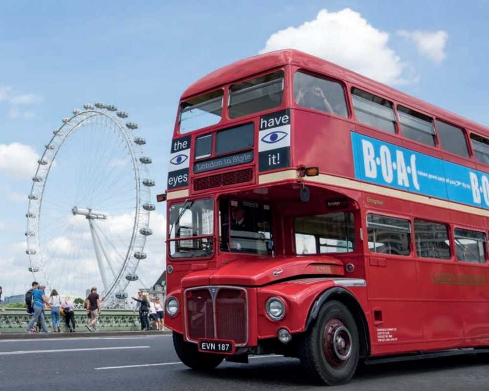 A red bus near the London Eye used for the London in Style tours.
