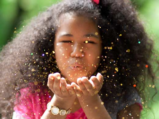 Little girl with her eyes closed blowing gold fairy dust out her hands.