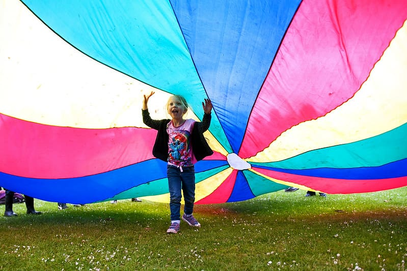 Young girl running under a colourful parachute playing games.