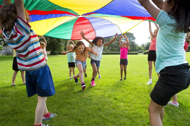 Children outside playing parachute games Two girls are running underneath while the others hold it up.