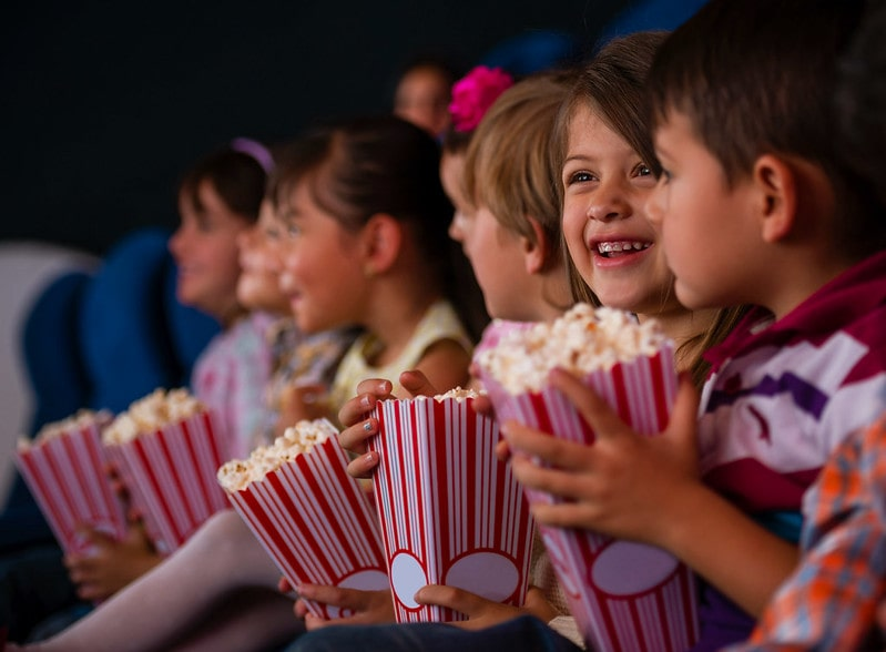Young kids sat in a cinema eating popcorn.