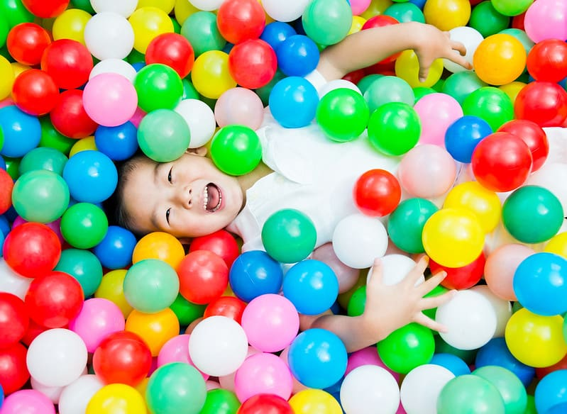 Young boy lying in a ball pit of colourful soft balls.