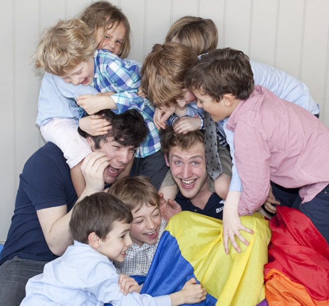 Lots of kids pile on top of two guys who are holding a parachute.