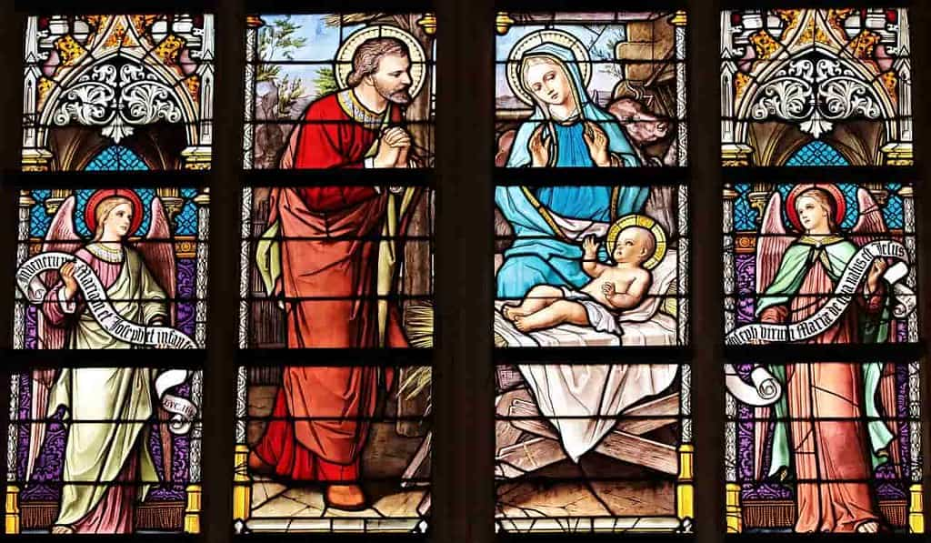 Stained glass church window depicting a colourful scene of the baby Jesus.