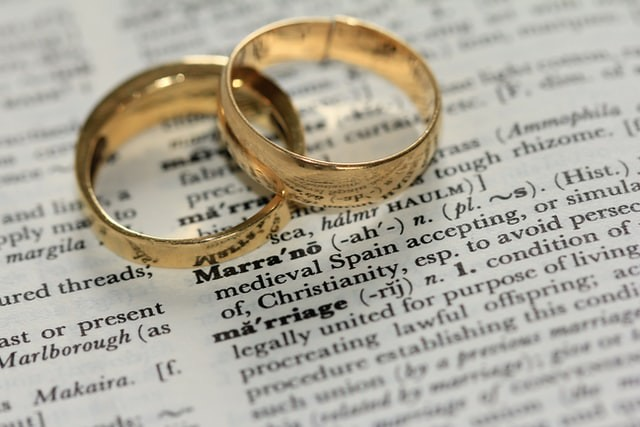 Two gold wedding bands lying on the page in a dictionary containing the definition of marriage.
