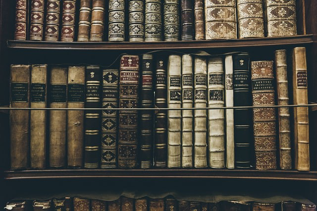 Old bound books sitting on the bookshelf.
