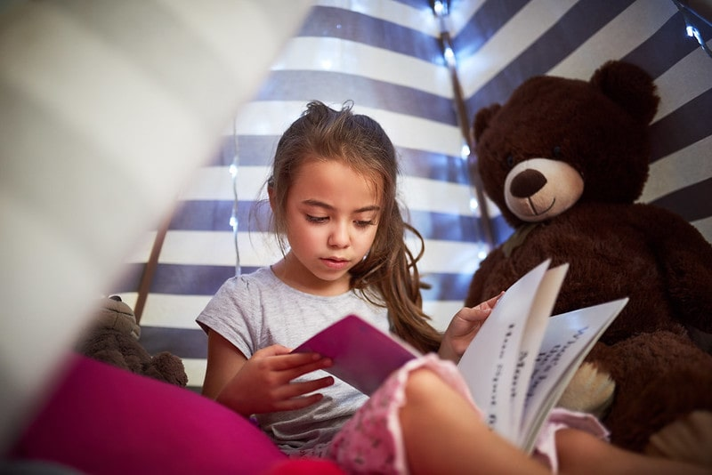 Little girl reading a book inside a tent at home, sitting next to her brown teddy bear.