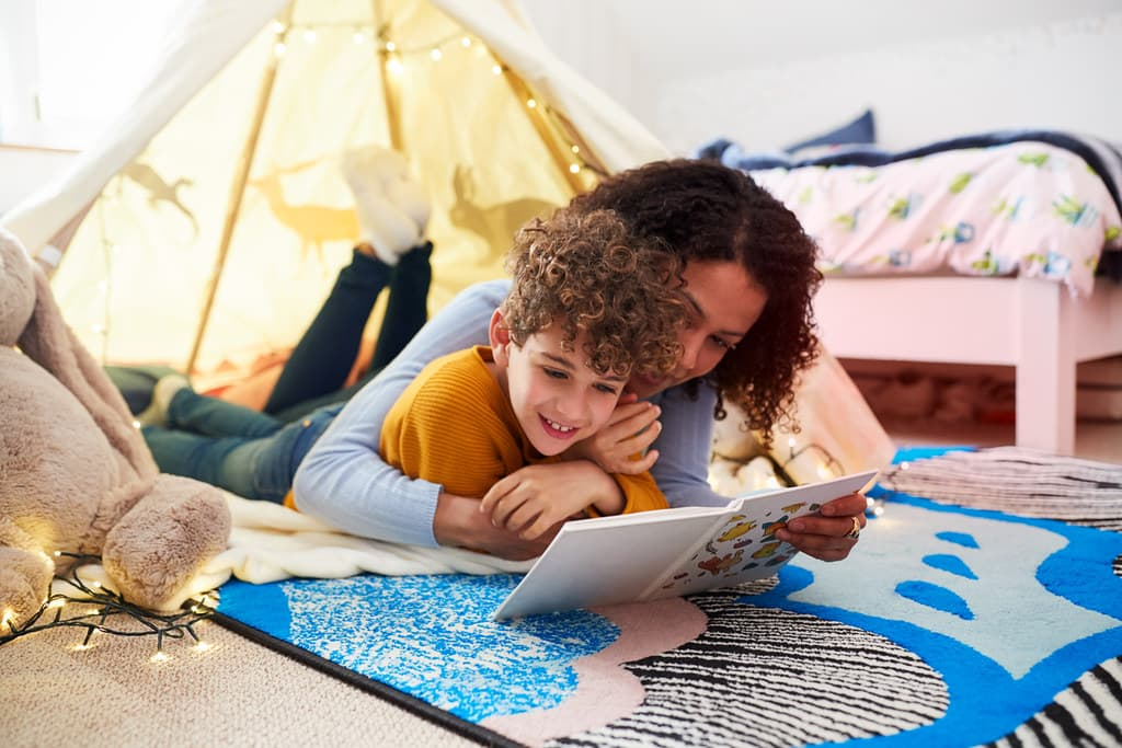 Mum reading a non-fiction book with her son in a den in his bedroom.