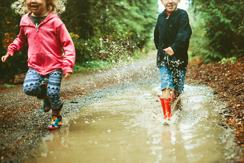 kids wearing rain boots splash and play in a big mud puddle