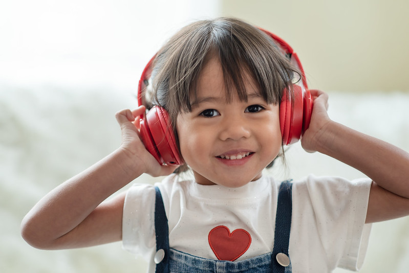 child enjoys listening with headphones