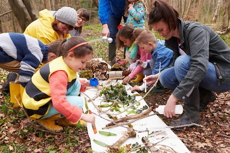 Group of children and adults doing an activity in the woods, looking at minibeasts.