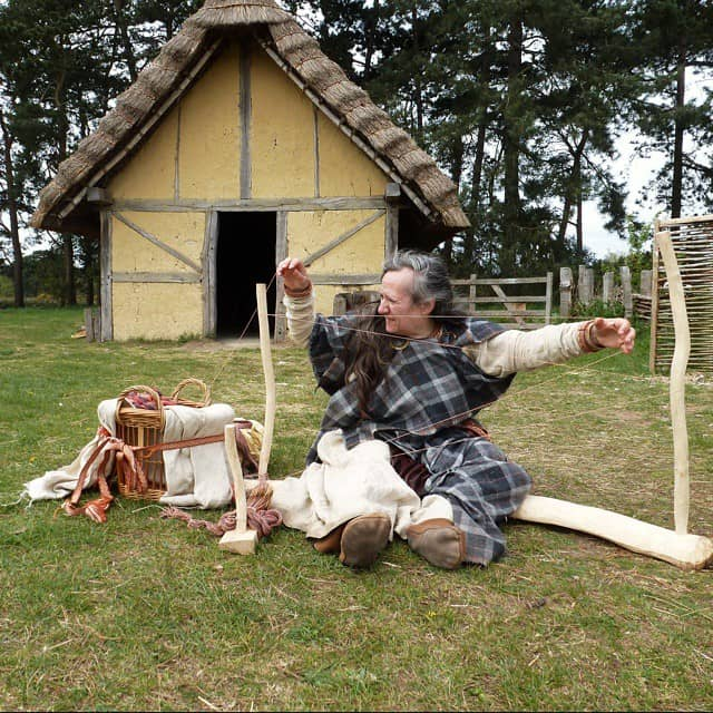 Woman in Anglo-Saxon village dressed as an Anglo-Saxon sat on the ground weaving.