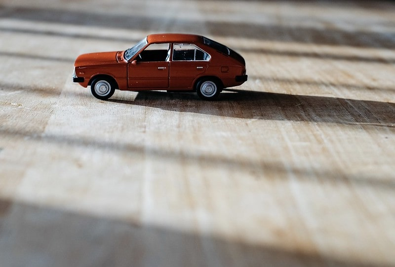 Red toy car on the wooden floor.