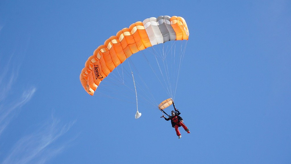 Man skydiving with an orange parachute is being pulled back down to the ground by gravity.