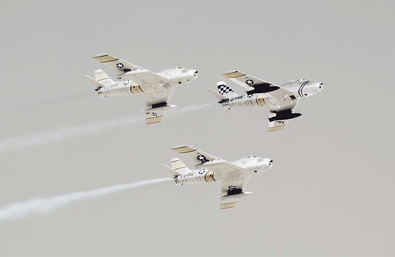 Three black and white planes flying through the air.