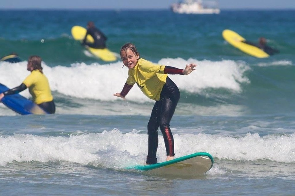 Kid standing on a surfboard in the sea riding the waves.