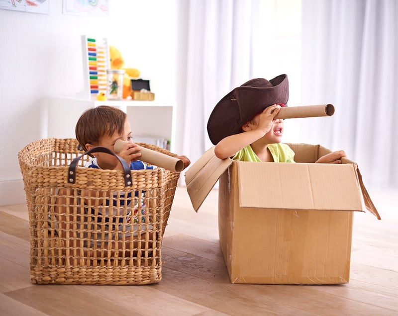 Two boys playing at home pretending to be pirates, sat in makeshift pirate ships made of a box and a basket.