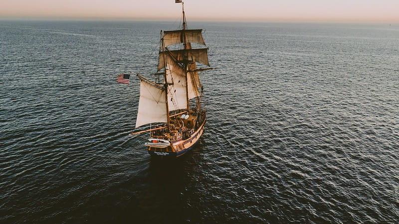 American pirate ship at sea sailing towards the horizon at sunset.