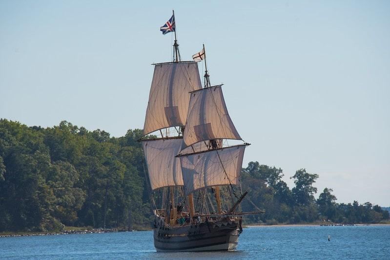 British pirate ship sailing away from an island.