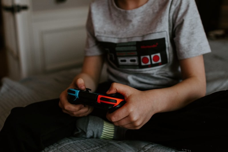 Young boy playing video games on his games console.