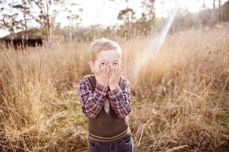 Boy in a field standing and laughing at Shrek jokes.