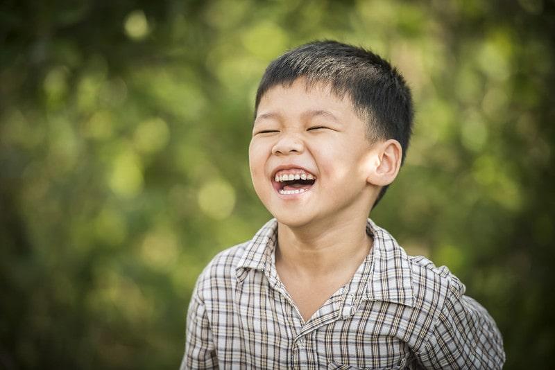 Boy outside laughing at Shrek jokes.